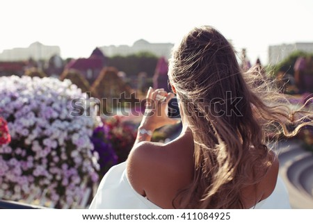 Tourist taking travel picture with phone in flowers park with gentle sun flare coming. Unrecognizable female young adult enjoying summer vacations in sexy white dress. (focus on shoulder) - stock photo