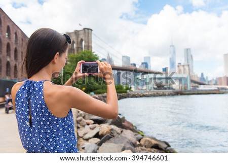 Tourist taking travel picture with phone of Brooklyn bridge and New York City skyline during summer holidays. Unrecognizable female young adult enjoying USA vacations in blue dress. - stock photo