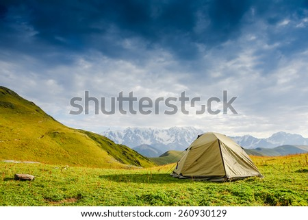 Tourist tent in camp among meadow in the mountain - stock photo