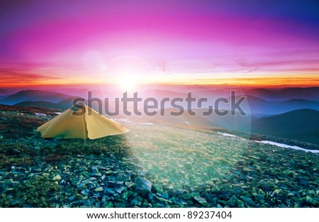 Tourist tent in the rocky mountains and flaring sun on the red horizon - stock photo