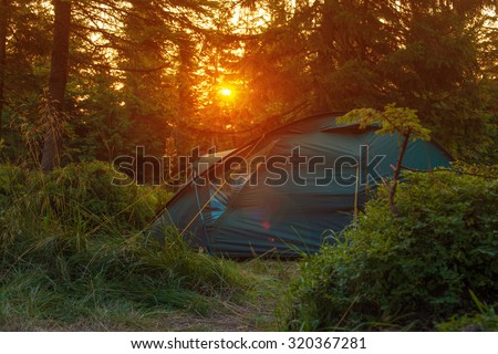 Tourist  tent stands in the rays of setting sun on the background of coniferous forest in the mountains. Tent in backlit . Wonderful landscape sunset in the mountains.   - stock photo