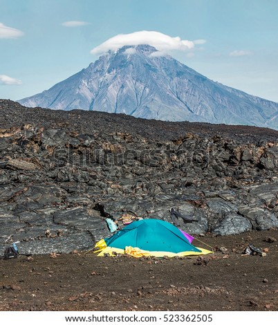 Tourist tent stands next to active lava flow from a new crater on the slopes of volcanoes Tolbachic, on background volcano Bolshaya Udina - Kamchatka, Russia