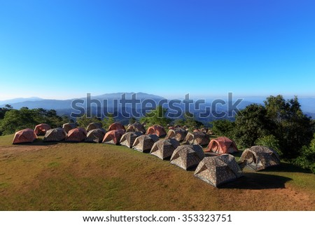 Tourist tents in camp among meadow in the mountain. - stock photo
