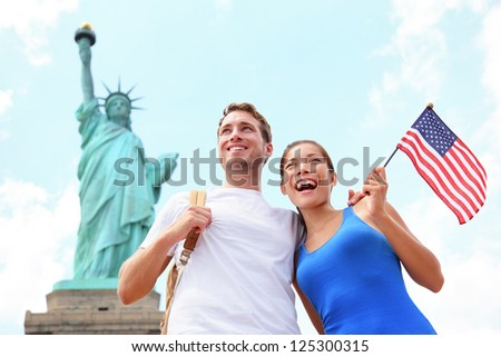Tourist travel couple at Statue of Liberty, New York City, USA. Multiracial tourist couple on summer vacation holidays. Asian woman holding American flag smiling happy. - stock photo