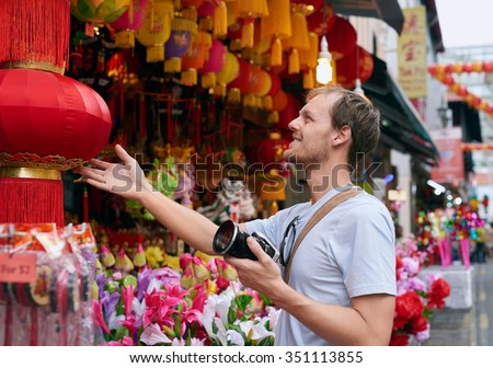 Tourist traveler with camera in modern asian city chinatown shopping looking at a red lantern for souvenir trinkets - stock photo