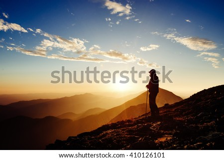 Tourist travels at the peak of the mountain rock. Sunny morning. Alps