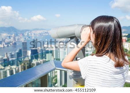 Tourist using binocular looking though Hong Kong skyline - stock photo