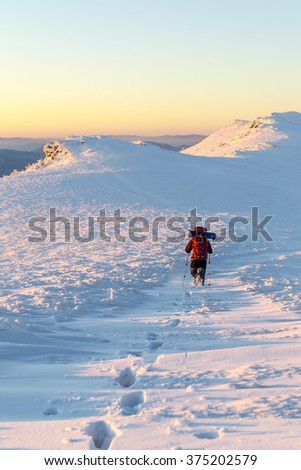 Tourist walking on a mountain ridge and left a trail in the snow. Evening. Winter hiking in the Carpathian mountains - stock photo