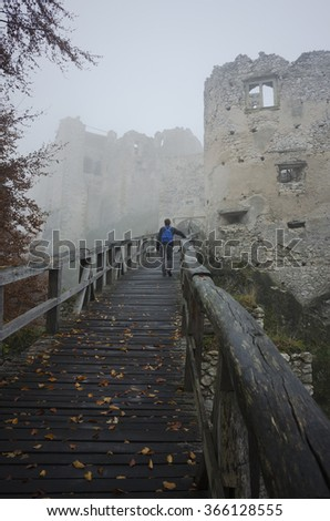 tourist walking on a wooden bridge leading to an old mystical castle ruin in fog,mist - stock photo