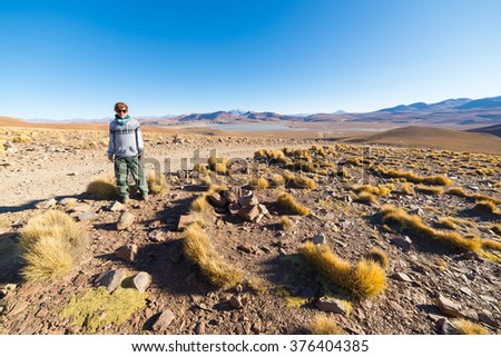 Tourist walking on the desert highlands of the Andes. Roadtrip to the famous Uyuni Salt Flat, important travel destination in Bolivia. Expansive landscape of barren mountain range and salt lakes. - stock photo