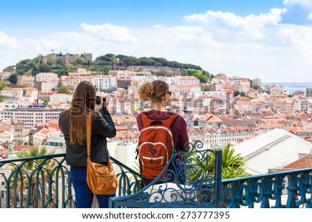 Tourist watching to Lisbon rooftop from Sao Pedro de Alcantara viewpoint - Miradouro in Portugal - stock photo