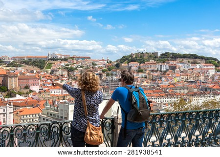 Tourist watching to Lisbon rooftop from Sao Pedro de Alcantara viewpoint - Miradouro in Portugal - stock photo