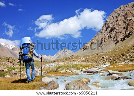 Tourist with a backpack and a mountain panorama - stock photo