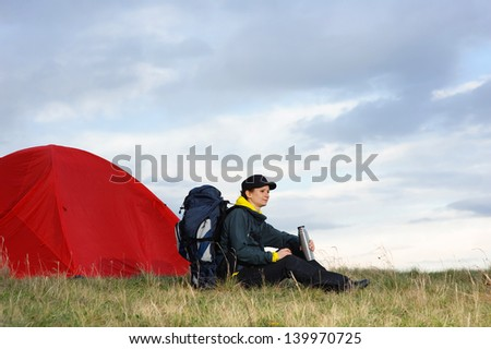 tourist with a backpack on the background of sky - stock photo