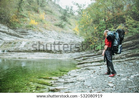 Tourist with a backpack standing on the river bank