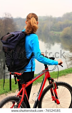 Tourist with a bike on a hill. Beautiful river views - stock photo