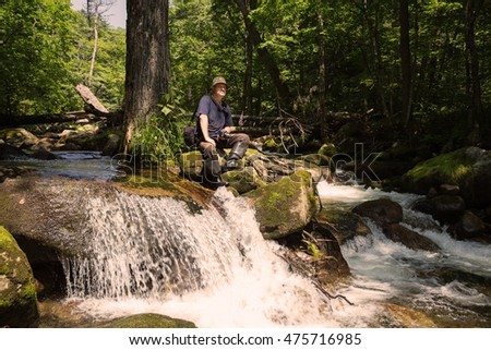 Tourist with a camera sitting on a stone near mountain river