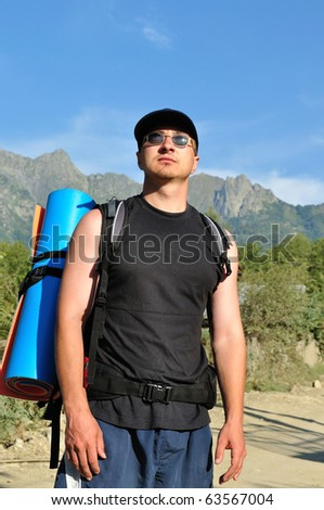 Tourist with a large backpack is a high mountain, on the way, full-face photos - stock photo