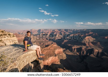 Tourist with backpack at Grand Canyon sitting on the rock edge, Arizona, USA