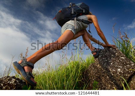 Tourist with backpack climbing a steep rock over blue sky background - stock photo