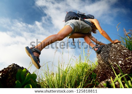 Tourist with backpack moving through rocky terrain - stock photo