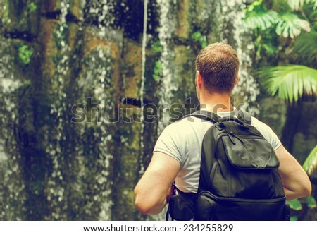 Tourist with backpack near waterfall. Vintage effect. Space for your text. - stock photo