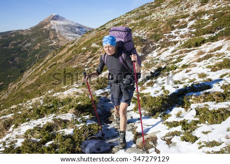 Tourist with backpack on a mountain trail goes.