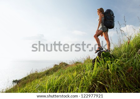 Tourist with backpack standing on a rock and looking to a sea