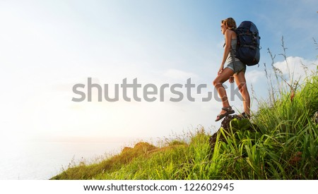 Tourist with backpack standing on a rock in a green meadow and looking to a sea - stock photo