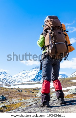 Tourist with backpack standing on a rock on clear sky background  - stock photo
