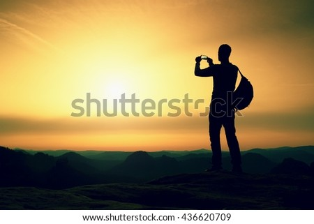 Tourist with backpack takes photos with smart phone on the rocky peak. Orange daybreak and fog in valley below - stock photo