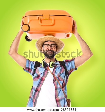 Tourist with baggage on hie head over colorful background - stock photo