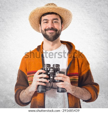 Tourist with binoculars over grey background - stock photo