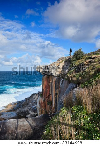 Tourist with camera standing on seaside cliff in Sydney - stock photo
