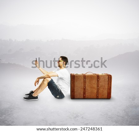 tourist with cellphone sitting near travel suitcase - stock photo