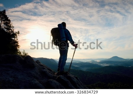 Tourist with heavy backpack and poles in hands stand on rocky view point and watching down to deep misty valley bellow. Sunny spring daybreak in rocky mountains. - stock photo