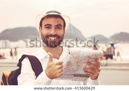 Tourist with map at Rio de Janeiro showing thumb up in vintage warm cinema look - stock photo