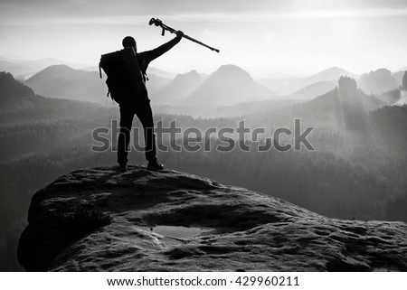 Tourist with medicine crutch above head achieved mountain peak. Hiker with broken leg in immobilizer.Deep misty valley bellow silhouette of man with hand in air. Spring daybreak. Black and white photo