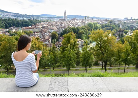 Tourist with smart phone camera in Bern, Switzerland at Rosengarten, the Rose Garden view. Woman taking photograph with smartphone at enjoying view of Berne landmarks and tourist attractions. - stock photo