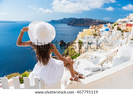 Tourist woman enjoying view of beautiful white village of Oia with Caldera and mediterranean sea. Young stylish female model wearing sunhat and red dress enjoying summer travel vacation in Europe. - stock photo