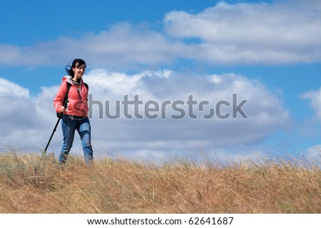 Tourist woman in mountains on the cloudy sky background - stock photo