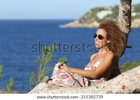 Tourist woman relaxing on the beach in vacations sitting on a tree with the ocean in the background - stock photo