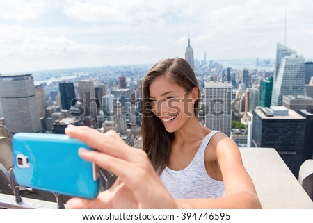 Tourist woman taking mobile phone selfie picture at New York skyline. Asian girl holding blue smartphone for self-portrait photo with view of Manhattan skyscrapers during summer travel vacation. - stock photo