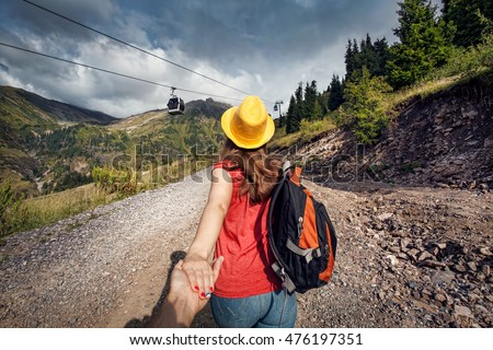 Tourist woman with backpack and yellow hat holding man by hand and walking down the road near cableway in the mountain valley