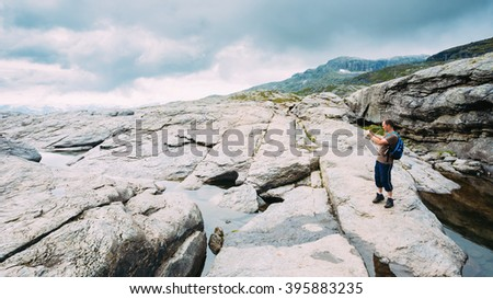 Tourist Young Man Photographs Beautiful Landscape Of Norwegian Mountains. Nature Of Norway. Travel And Hiking. Active Lifestyle. Amazing Scenic View. Scandinavia Travel. - stock photo