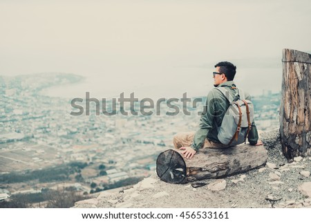 Tourist young man sitting on tree trunk and looking at town