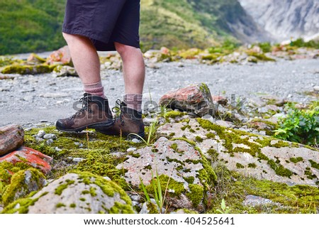 Tourist young man walking in Franz Josef Glacier, New Zealand South Island. Sport tourist boots - stock photo