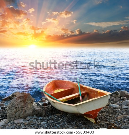 touristic  boat on a coast by a sunset - stock photo