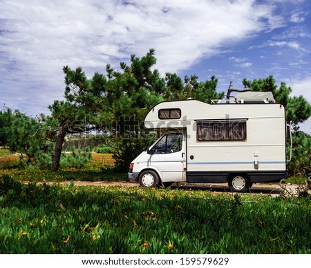 Touristic caravan staying in a forest. Comfort and freedom. - stock photo