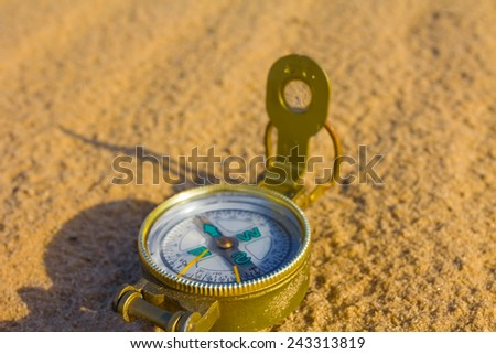 touristic compass on a sand background - stock photo